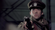 "Scott Norman wearing a uniform and holding a gun in ""The Wars of Other Men"" by Mike Zawacki."