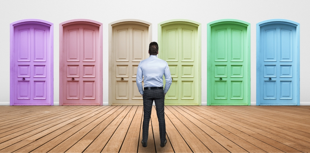 Businessman choosing a door. Credit iStock